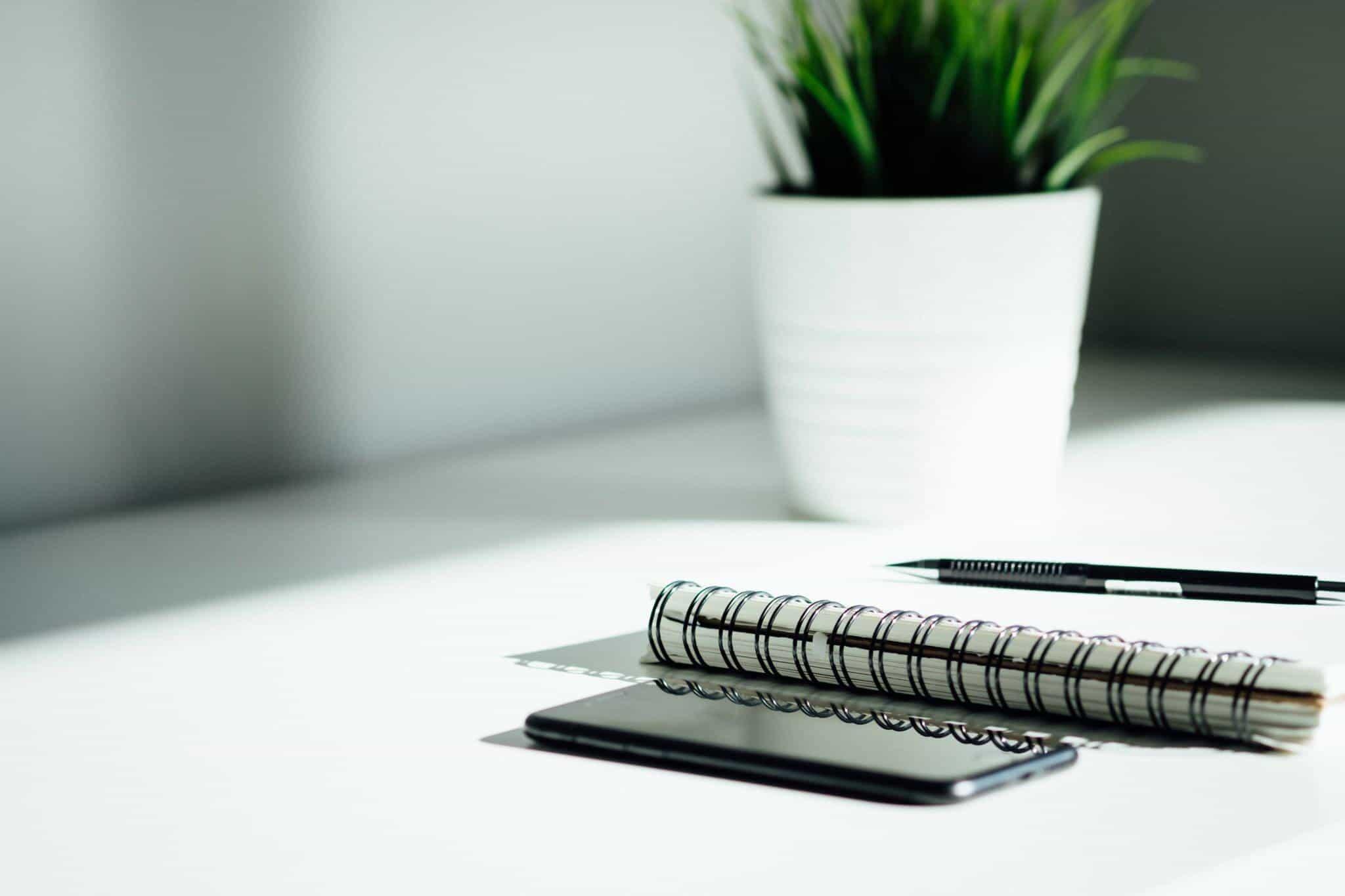 desk plant notebook pen phone